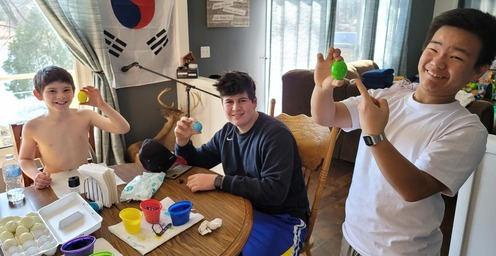 Two teenage boys and a little boy dying easter eggs