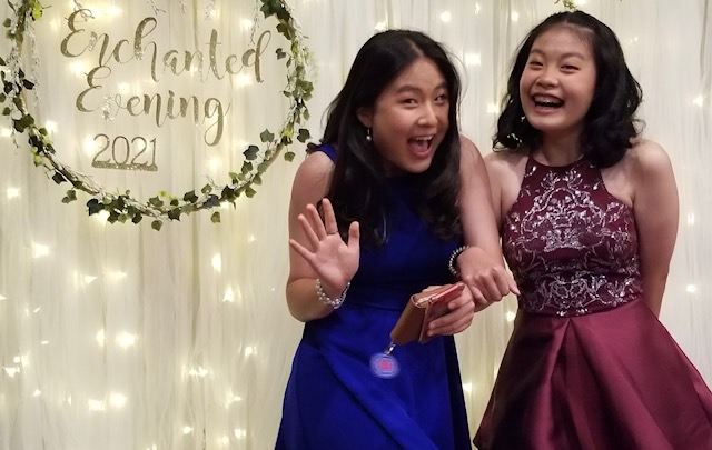 two asian teenage girls dressed for school dance smiling and laughing together