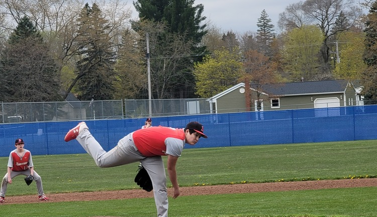 Teenage boy pitching for baseball game
