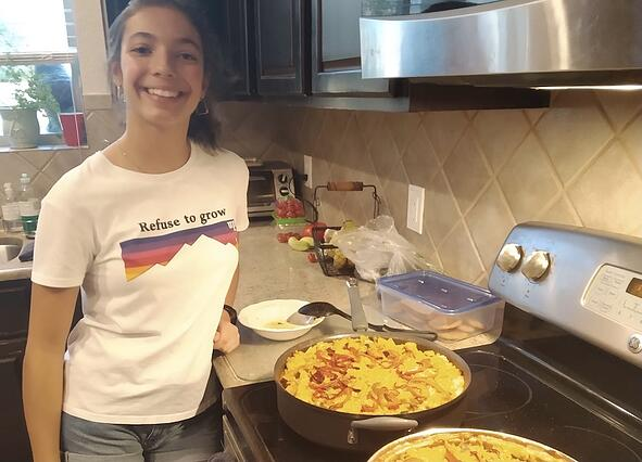 Spanish teenager standing by two fresh paellas