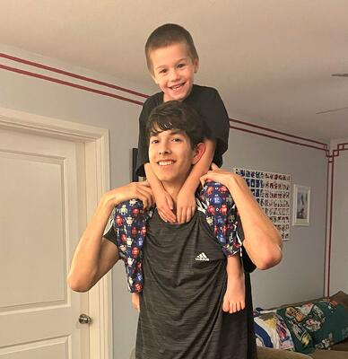 little boy on teen brother's shoulders