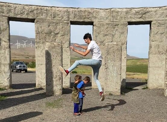 teen boy jumping over 2 little boys