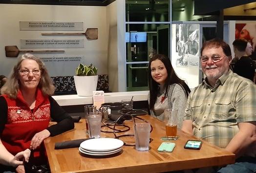 Brazilian exchange student in restaurant with host parents