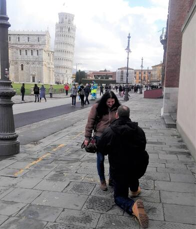 Bob on one knee proposing to Carla; Tower of Pisa in background