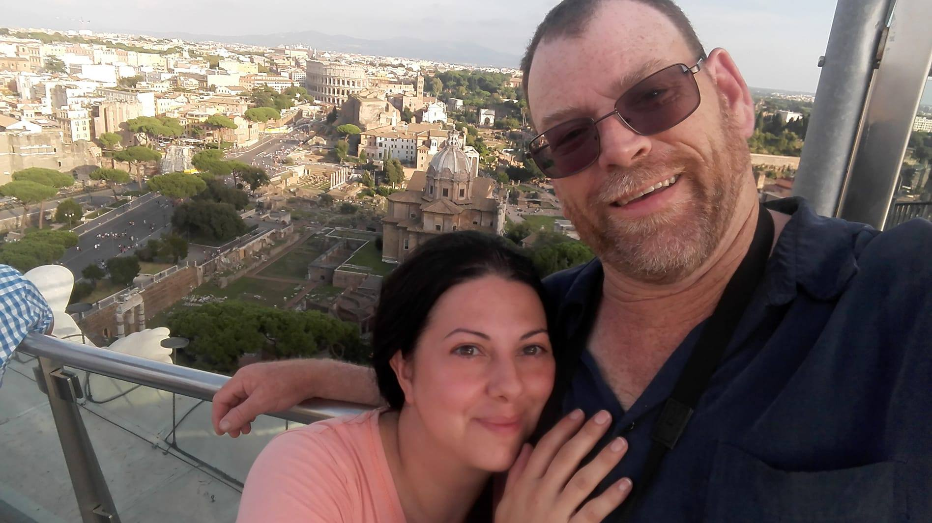 Selfie of Bob & Carla in Rome with the Colosseum behind