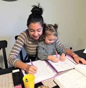 toddler doing homework with teen