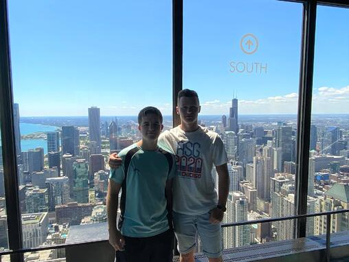 boys in front of large window with Chicago skyline behind