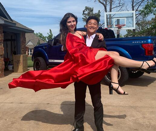 Chihok in a tux holding date in a flowing red dress
