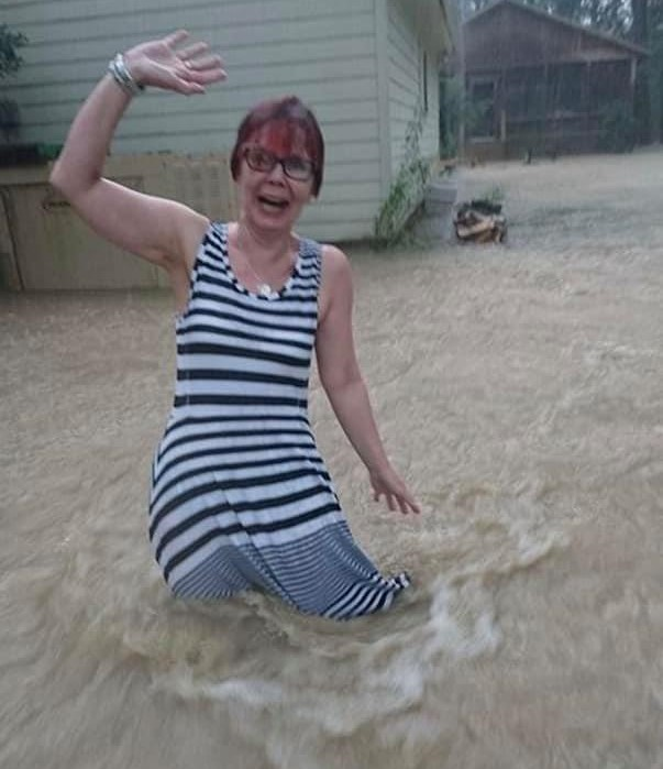 woman standing in flood waters in a dress