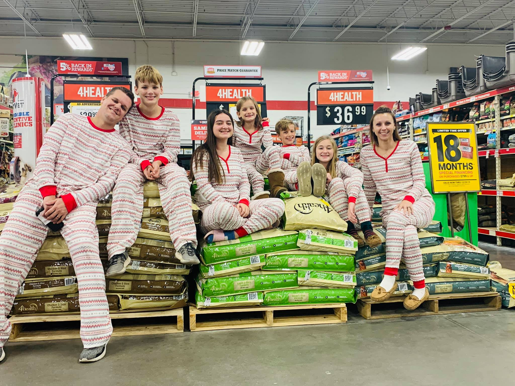 Family in matching pjs sitting on stacks of dog food bags
