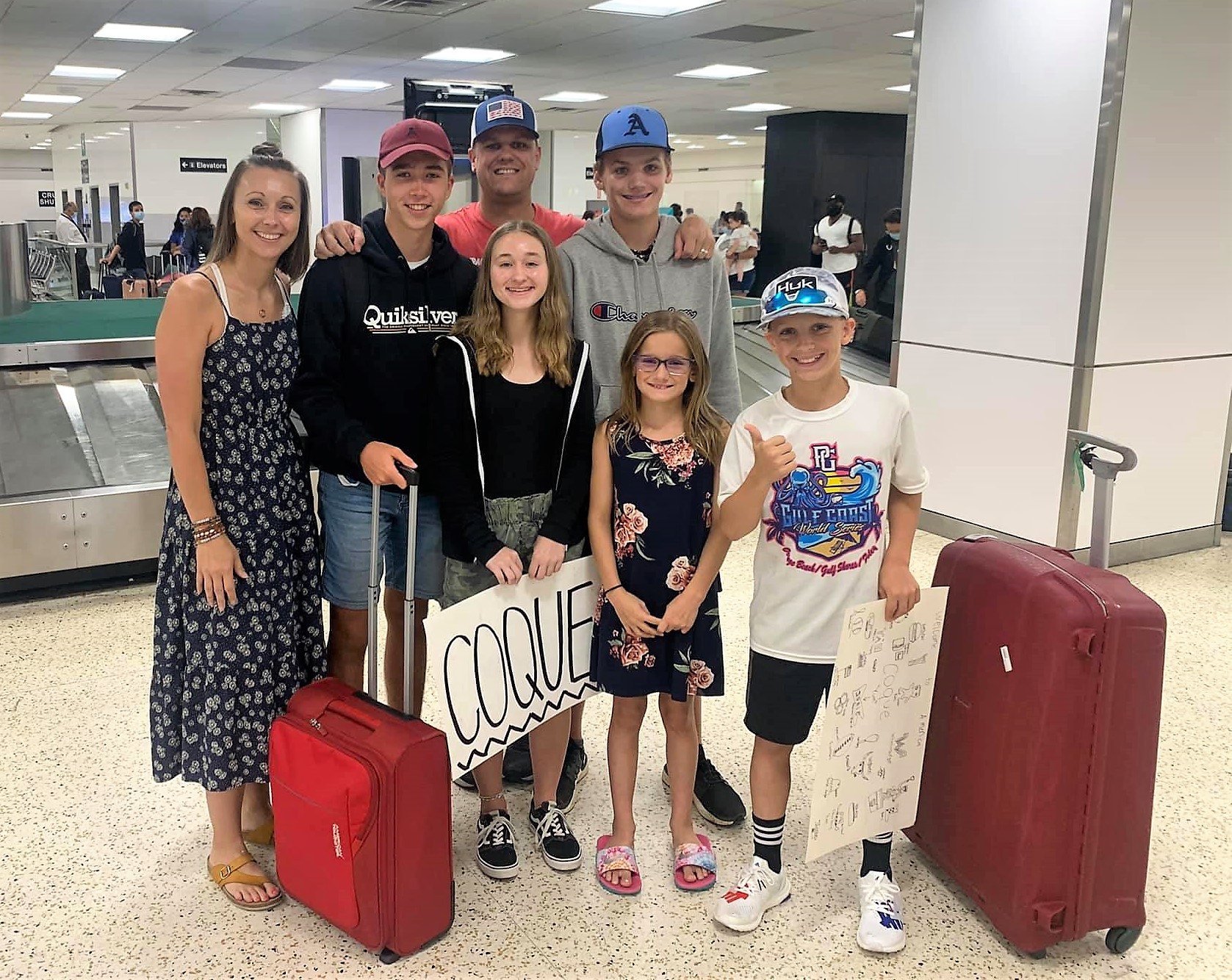 family standing with exchange student at airport