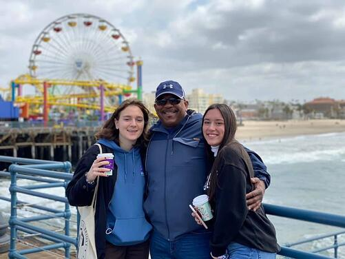 dad and two teen girls in front of amusement park