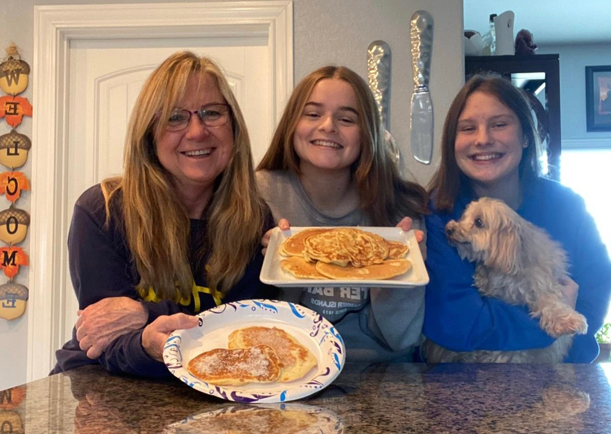 mother and two daughters with plates of  German pancakes
