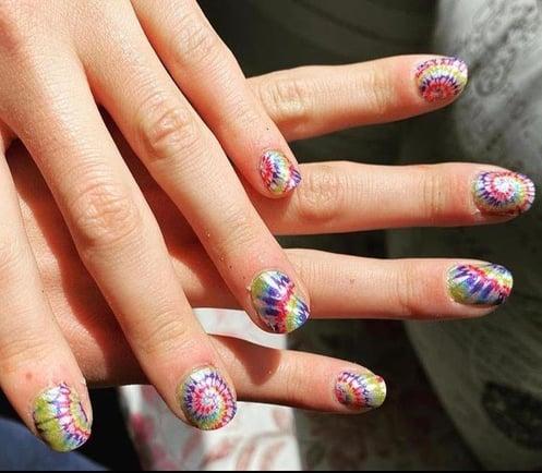 fingernails painted in rainbow design