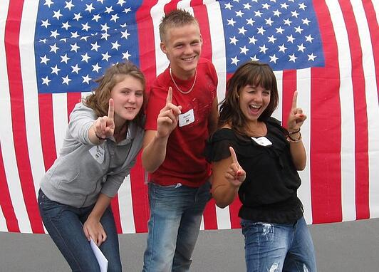 three teens in front of American flags