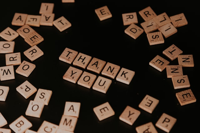 Game pieces show the word Thank You to talk about cross cultural gratitude and saying thank you in the USA