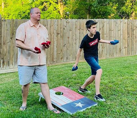 Dad and teen boy playing corn hole