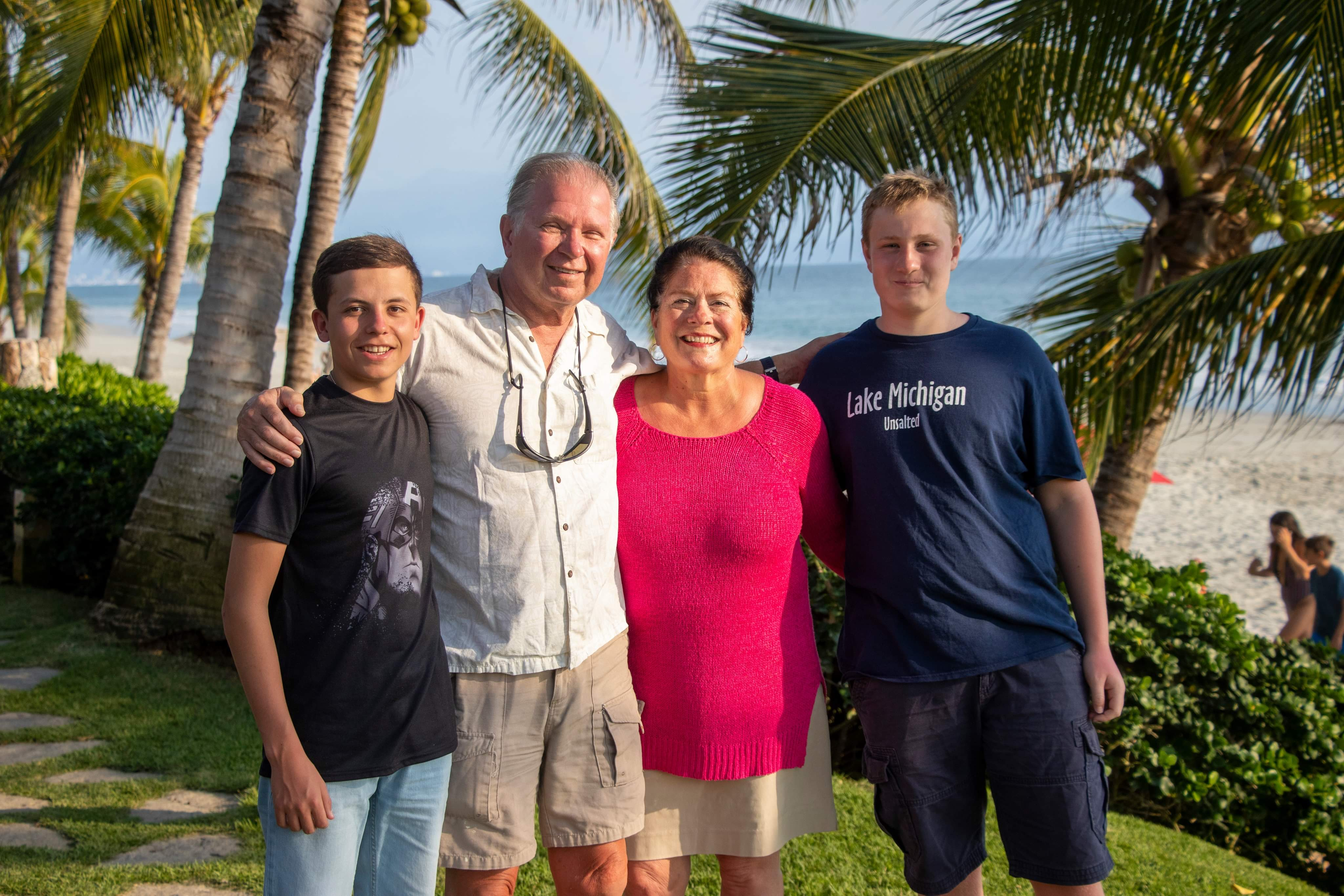 two teen boys with older parents at the beach