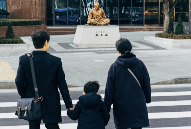 Korean mother, father and small son approaching temple