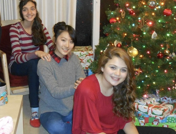 South Korean exchange student with host sisters and Christmas tree