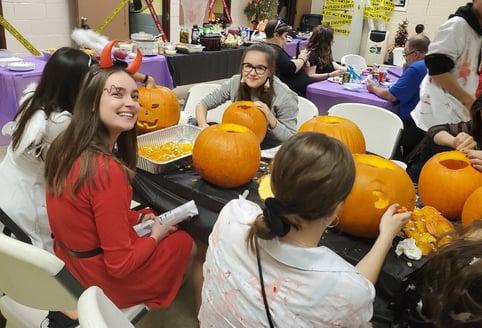 Ivona in a devil costume carving a pumpkin
