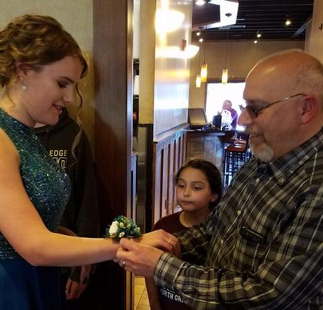 Dad putting corsage on teen girl's wrist