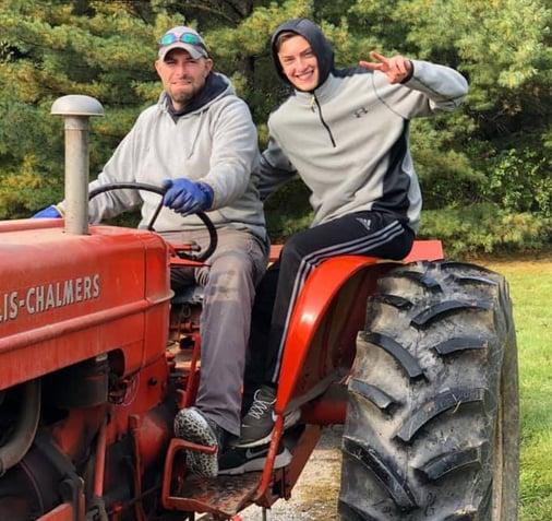 Dad giving teen boy a tractor ride