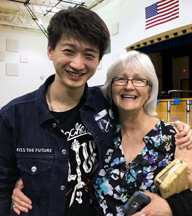 Asian boy with arm around smiling older teacher