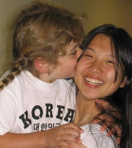 young girl kissing Korean exchange student's cheek
