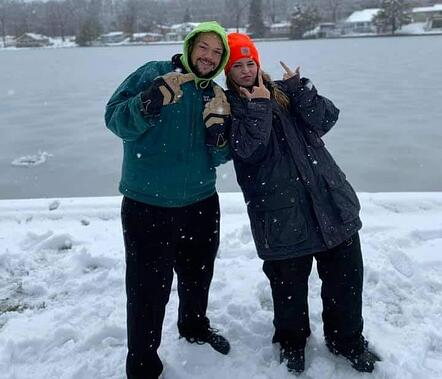 dad and teen girl doing hand sign pose in front of lake