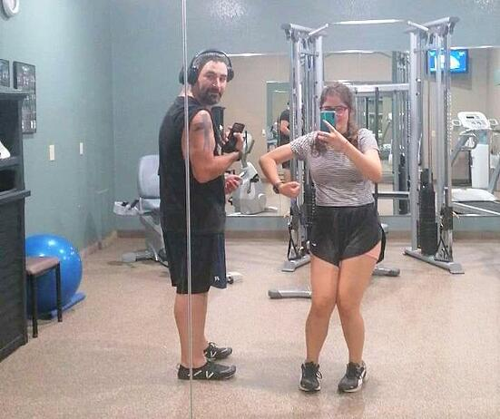 Dad and teen girl in gym comparing biceps