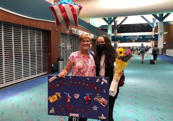 woman and exchange student at airport with sign and balloons