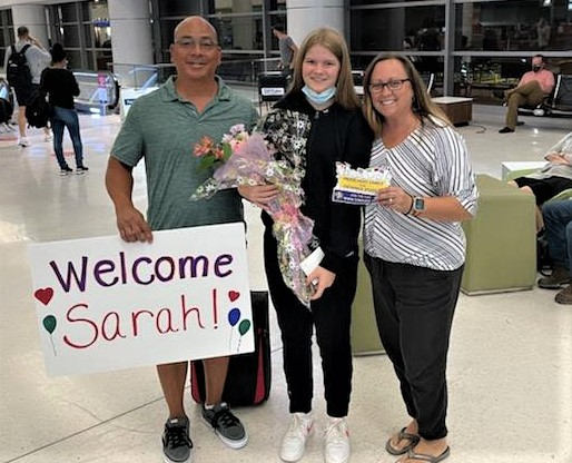 host parents and student with welcome sign at airport