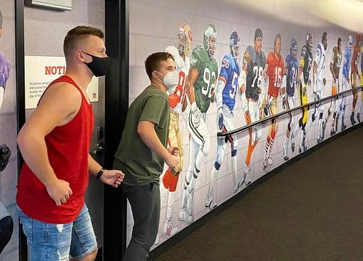 boys prentending to be part of football mural