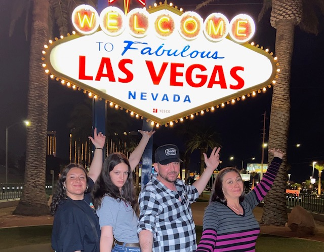 Parents and two daughters in front of Welcome to Las Vegas sign