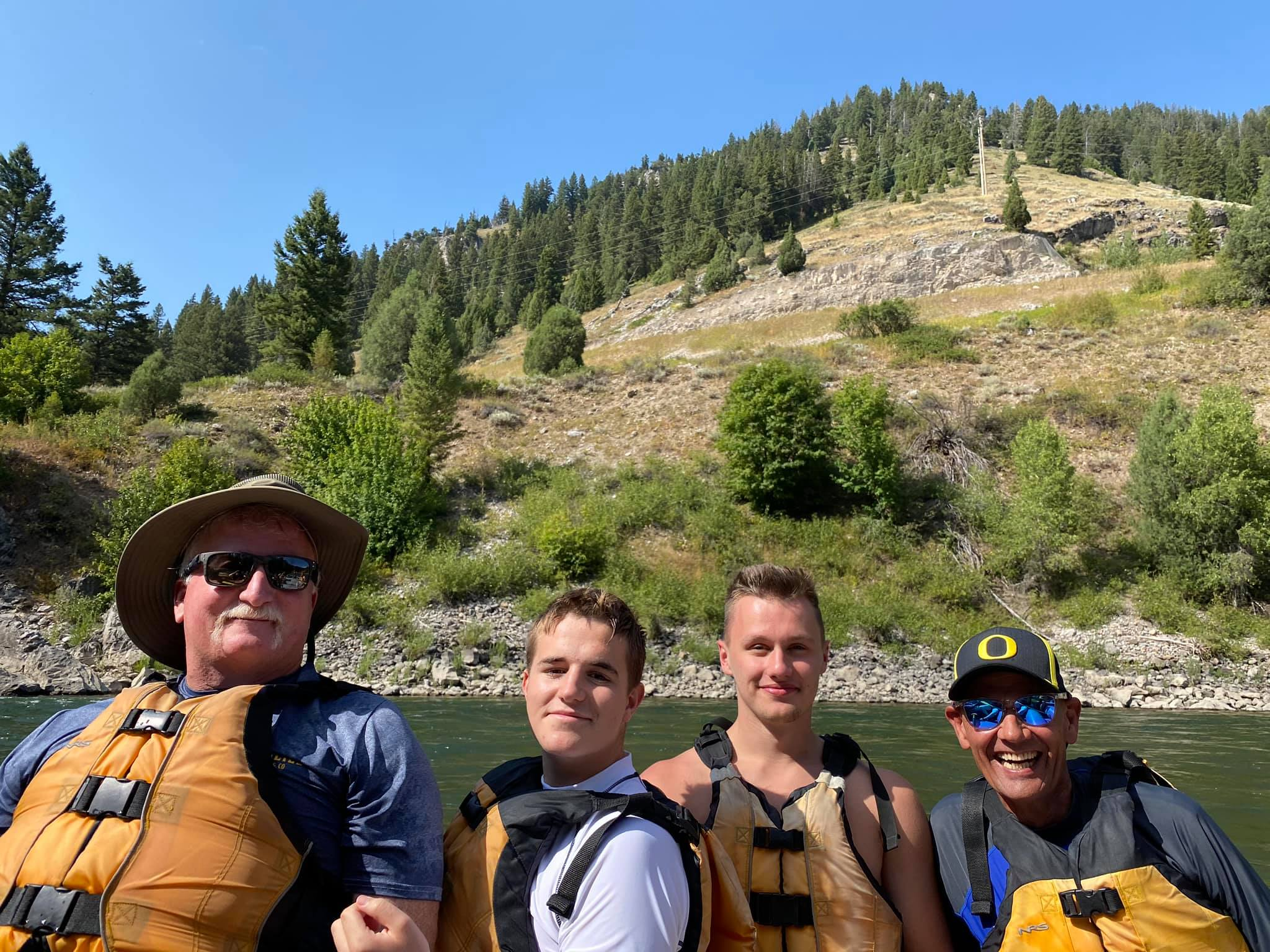 two fathers with two sons river rafting