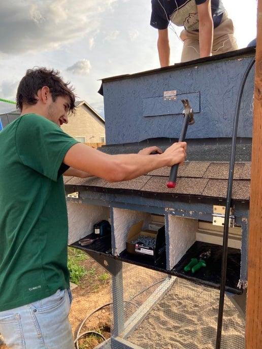 teen boy building chicken coop