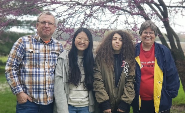 smiling parents with two asian teenagers they are hosting