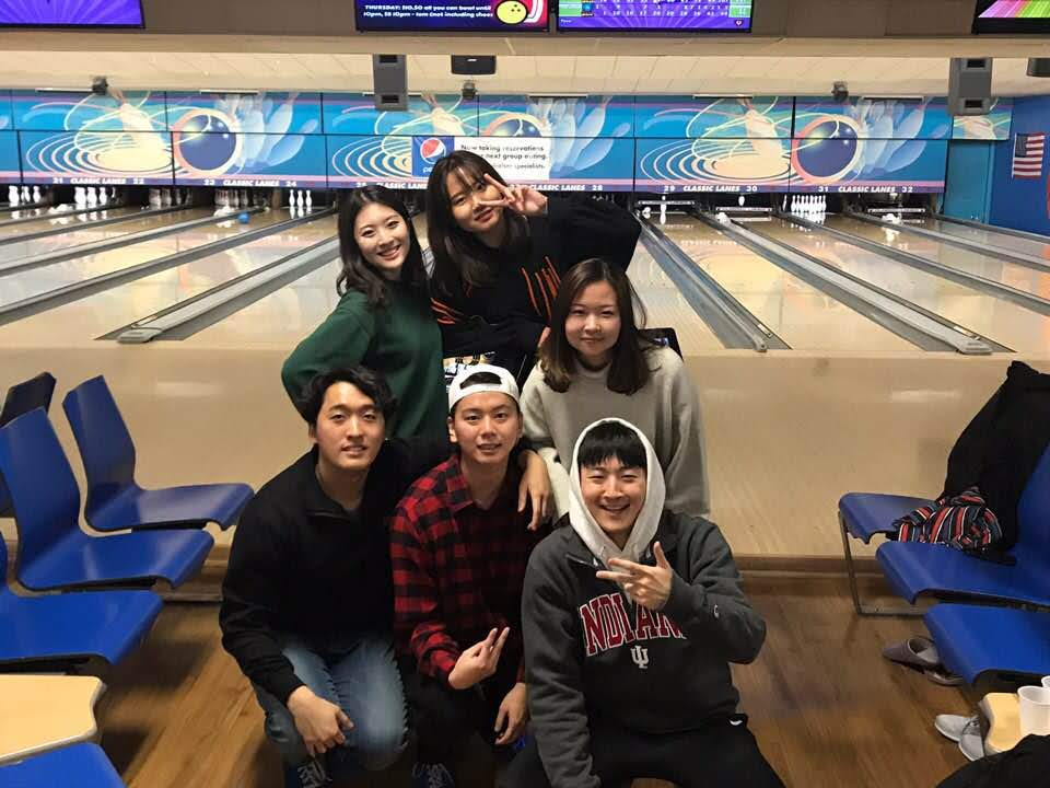 South Korean exchange students at a bowling alley posing in front of a lane