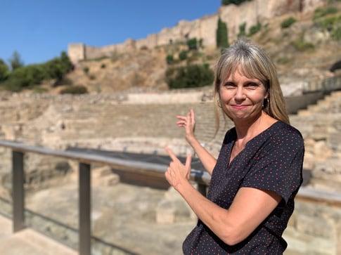 Brenda Padilla Ericksen pointing to Roman Ruins in Malaga (and the Alcazaba)