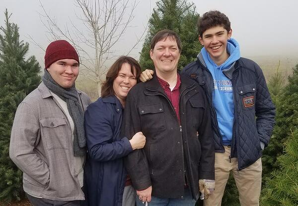Thomas and host family with trees in the background