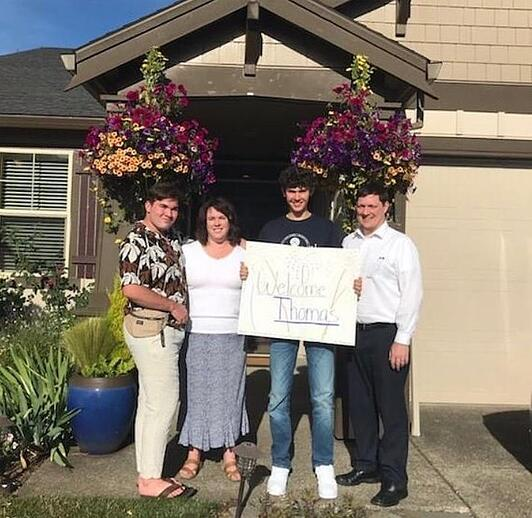 family and student in front of home with welcome sign