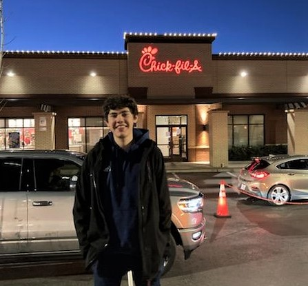 Thomas smiling in front of Chik-fil-A