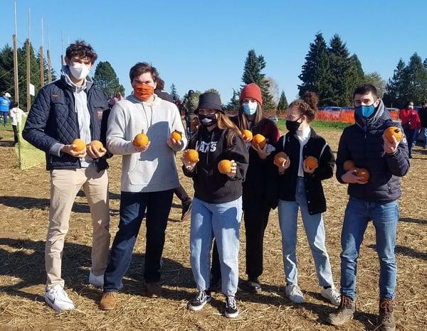 teens holding mini-pumpkins at a pumpkin patch