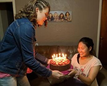 girl holding birthday cake for exchange student