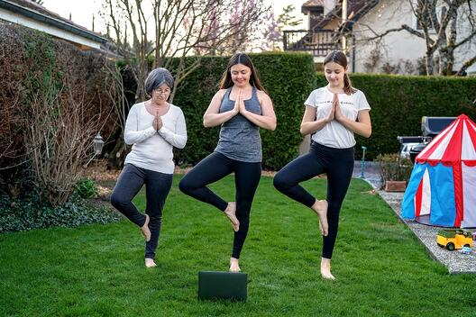 mom and two daughters doing yoga in yard