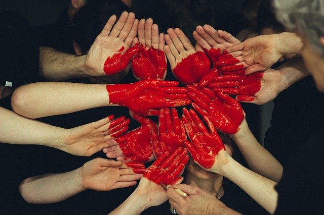 Many hands together with a big red heart painted on them