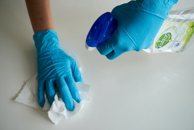 hands wearing blue rubber gloves cleaning counter with spray bottle