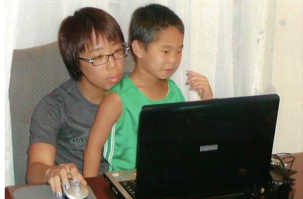 big brother with little brother on lap in front of computer