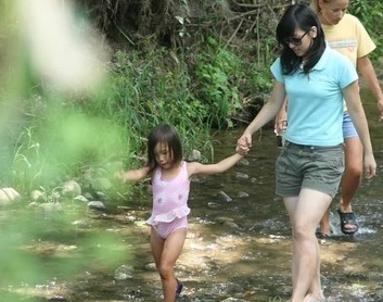 big sister and little sister holding hands and walking in nature
